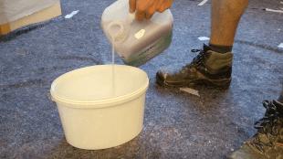 Der Tiefengrund wird in den Kübel gegossen und mit Wasser verdünnt