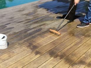 Holz-Entgrauer mit einer Bürste oder einem Besen von der Oberfläche waschen.