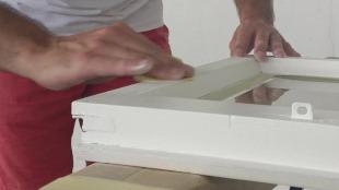 Erneutes Schleifen des Fensterflügels aus Holz mit Schleifpapier der Körnung 180.